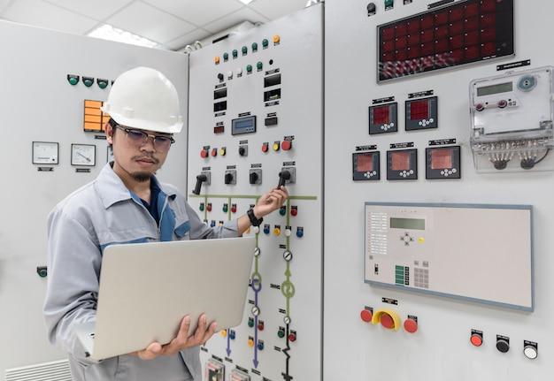 Инженер работает и проверяет состояние распределительного устройства распределения электрической энергии в помещении подстанции электростанции