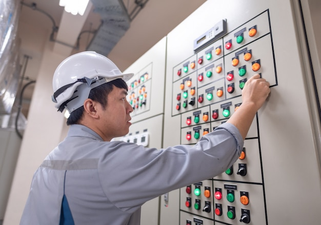 Engineer working and check status switchgear electrical energy distribution at substation room of power plant