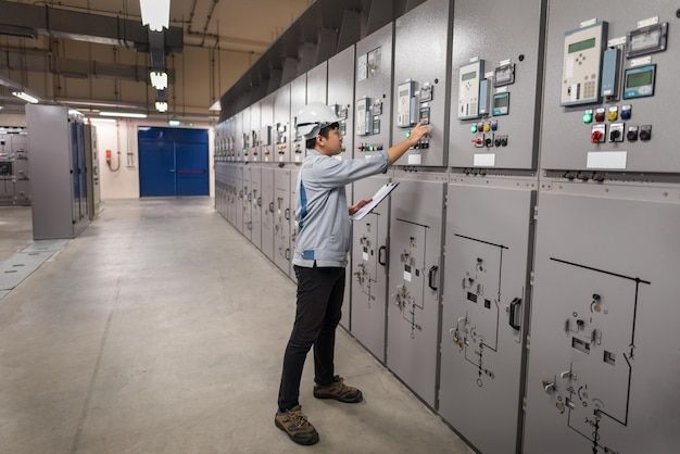 Engineer working and check status switchgear electrical energy distribution at substation room