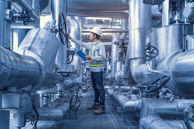 Инженер работает с обратным клапаном и трубами на заводе, стальные трубопроводы и клапаны в промышленной зоне, инженер по обслуживанию оборудования на электростанции