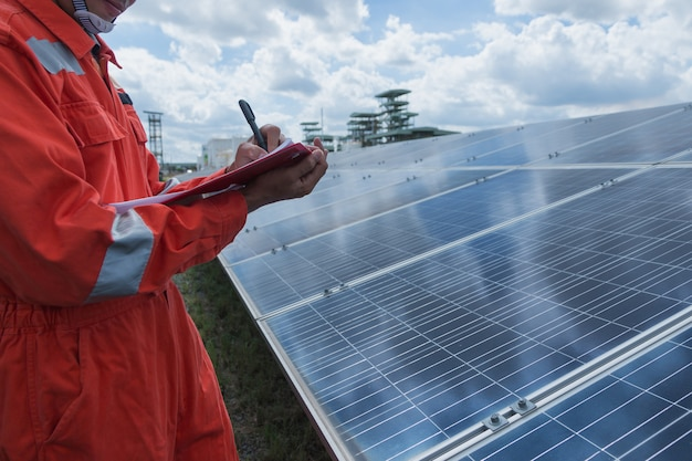 Engineer working on checking and maintenance electrical equipment at solar power plant ;engineer checking solar panel in routine operation  at solar power plant