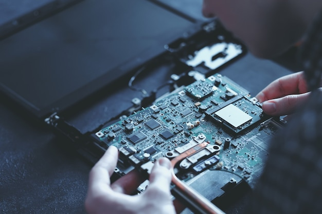 Engineer working on disassembled laptop