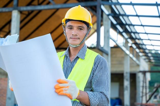 Инженер работает над новым проектом строительства чертежей на строительной площадке, серьезный инженер-строитель работает с документами на строительной площадке.