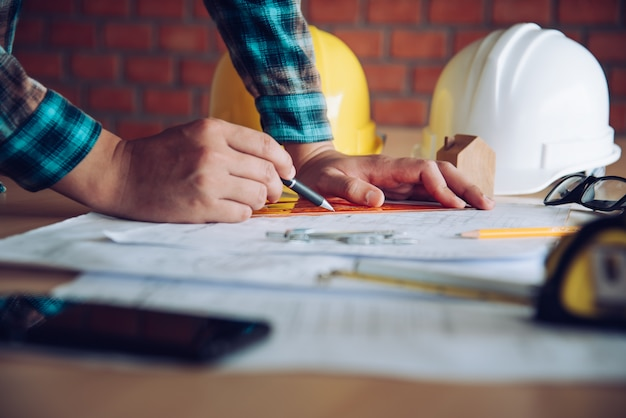 Engineer working in office with blueprints, inspection in workplace for architectural plan, construction project ,business construction concept.