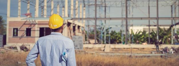 Инженер работает на строительной площадке с чертежом документа