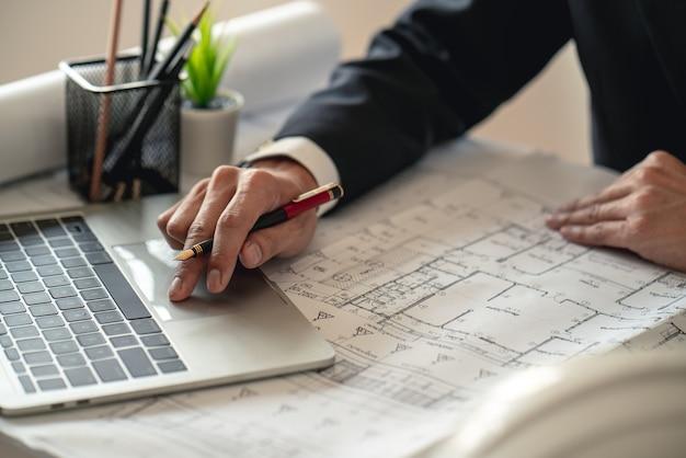 Инженер, работающий на строительной площадке с чертежным документом