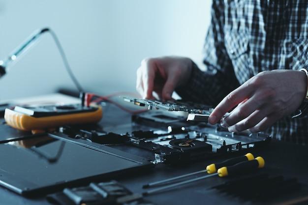 分解されたラップトップに取り組んでいるエンジニア