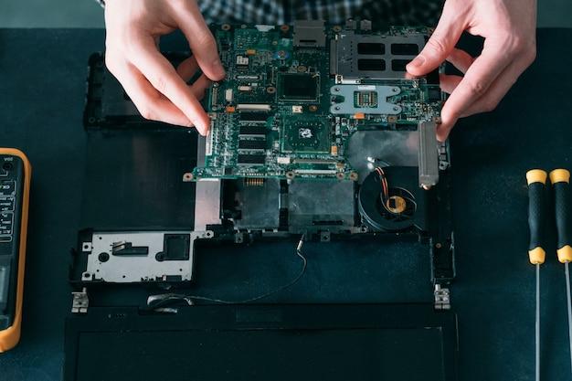 분해 된 노트북에서 작업하는 엔지니어