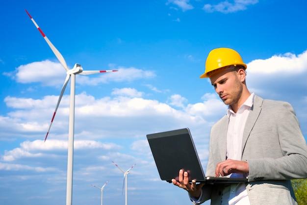 풍력 발전기 앞에서 자신의 노트북에서 작업하는 엔지니어