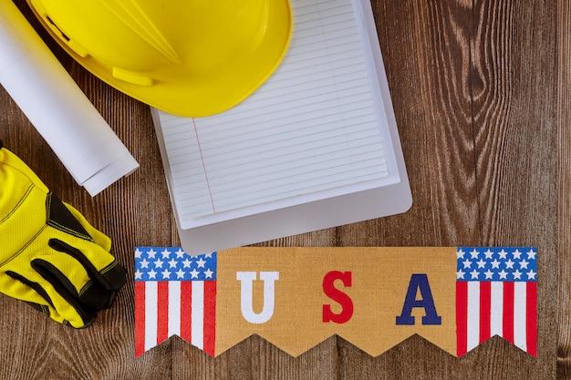 労働者の日に空白のノートブック建設保護黄色安全ヘルメット付きのオフィスの机で働くエンジニアは、連邦の祝日米国です。