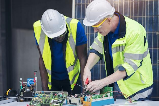 ソーラーパネルの背景を持つ電気パネルの修理、コンセプトチームワーク、または再生可能エネルギーのトレーニングを行うエンジニア。