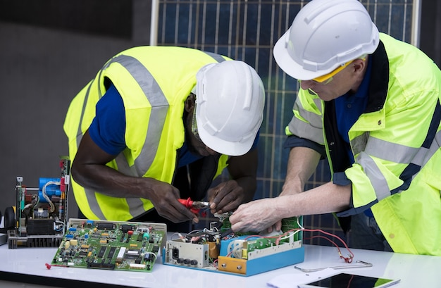 Engineer working repairing electric panel with solar panels background, concept teamwork or training of renewable.