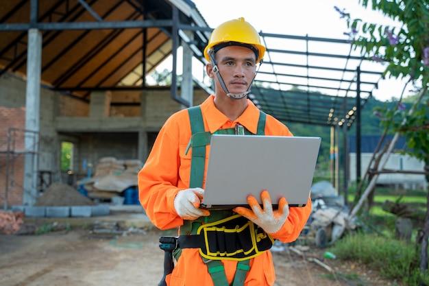 Инженер, работающий с ноутбуком над архитектурным проектом на строительной площадке.
