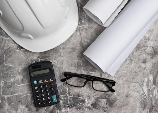 Рабочее место инженера. строительный шлем, рулоны чертежей, калькулятор и очки на сером бетонном фоне. вид сверху. копировать пространство