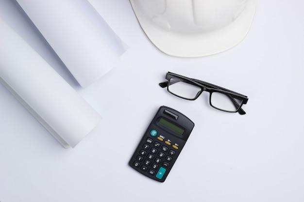Рабочее место инженера. строительный шлем, рулоны чертежей, калькулятор и очки на белом фоне. вид сверху. копировать пространство