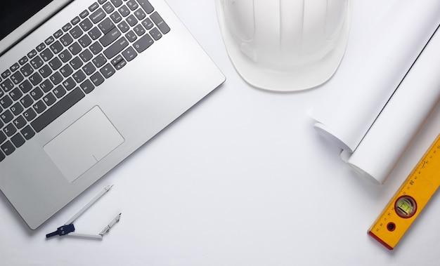 Рабочее место инженера. ноутбук, рулоны чертежей, инструменты на белом фоне. вид сверху. копировать пространство