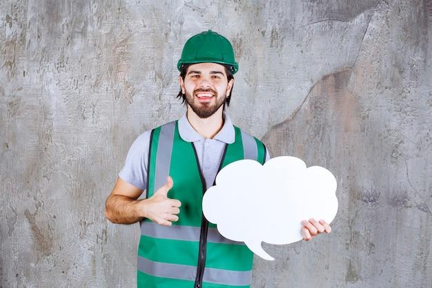 Ingegnere con equipaggiamento giallo e casco che tiene in mano una bacheca informativa a forma di nuvola e si gode questo progetto