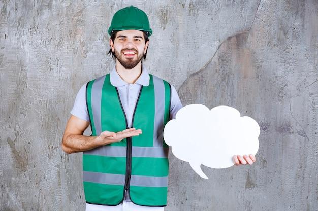 Ingegnere con equipaggiamento giallo e casco in possesso di un pannello informativo a forma di nuvola.