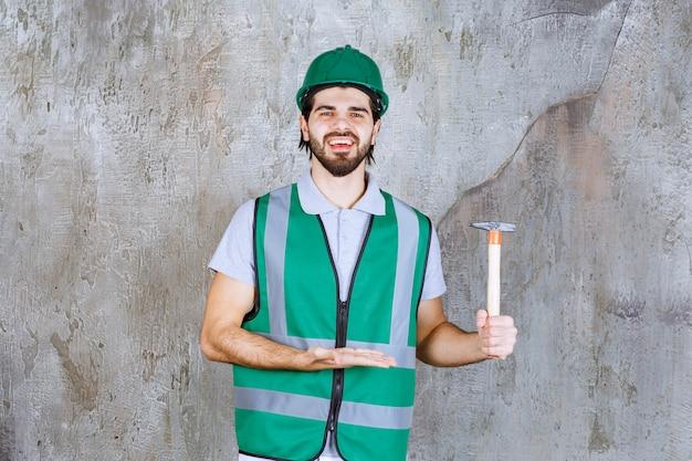 Ingegnere con equipaggiamento giallo e casco che tiene in mano un'ascia con manico in legno.