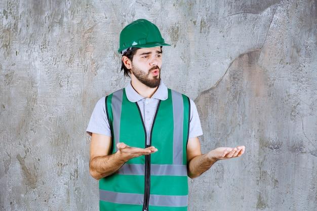 Ingegnere in marcia gialla e casco in piedi sul muro di cemento e interagisce con la persona davanti.