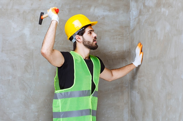 Engineer in yellow helmet and industrial gloves hitting the concrete wall with an ax