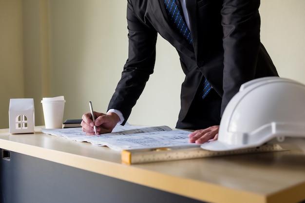 엔지니어링 사업가 관리자는 사무실에 흰색 헬멧을 쓴 테이블에 종이 청사진을 작성합니다. 비즈니스 감사 성공 프로세스입니다.