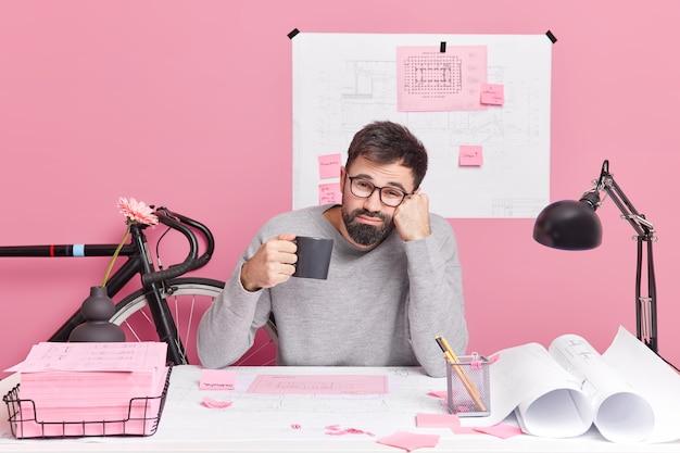 エンジニアリング建設と建築コンセプト。疲れた男性サラリーマンが一晩中さわやかなコーヒーを飲み、緊急の仕事でコワーキングスペースのデスクトップで仕事のポーズを終える期限があります。