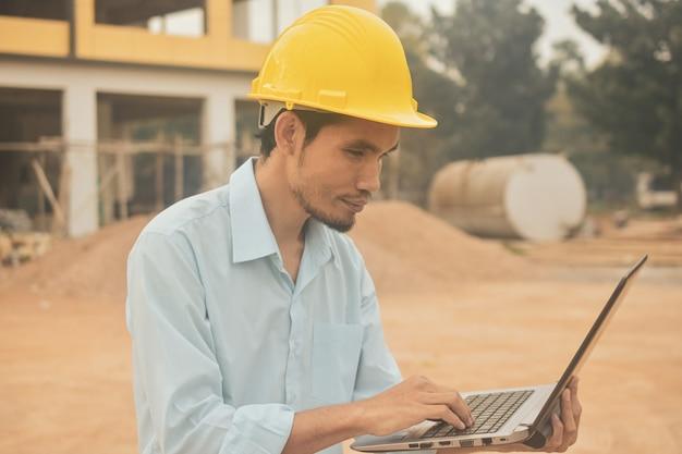 부동산 건설 프로젝트에서 컴퓨터 노트북 검사 작업을 들고 엔지니어링 건설