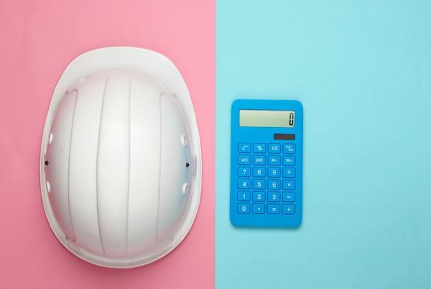 Каска инженерной строительной безопасности и калькулятор на голубой пастели. расчет стоимости ремонта или строительства дома. плоская планировка