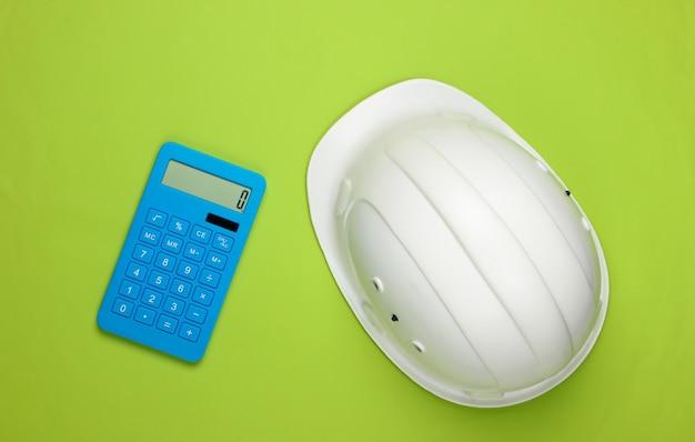 Шлем безопасности инженерной конструкции и калькулятор на зеленом цвете. расчет стоимости ремонта или строительства дома. плоская планировка