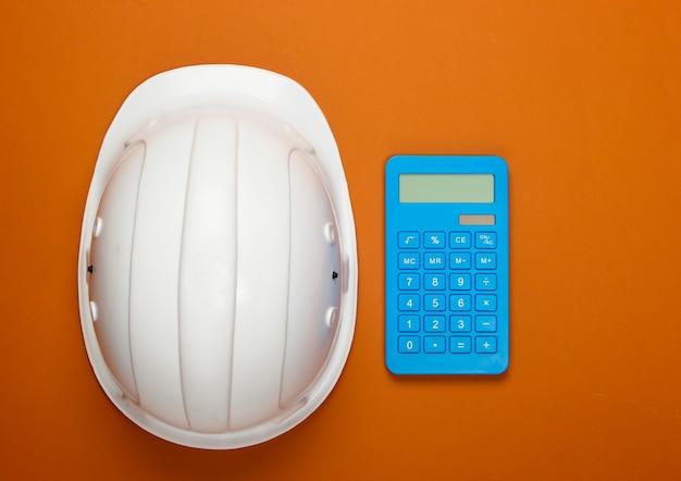 Шлем безопасности инженерного строительства и калькулятор на оранжевом. расчет стоимости ремонта или строительства дома. плоская планировка
