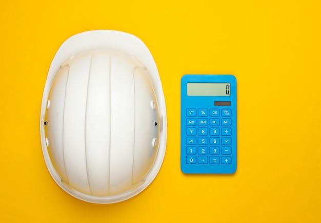 Шлем безопасности инженерного строительства и калькулятор на желтом. расчет стоимости ремонта или строительства дома. плоская планировка