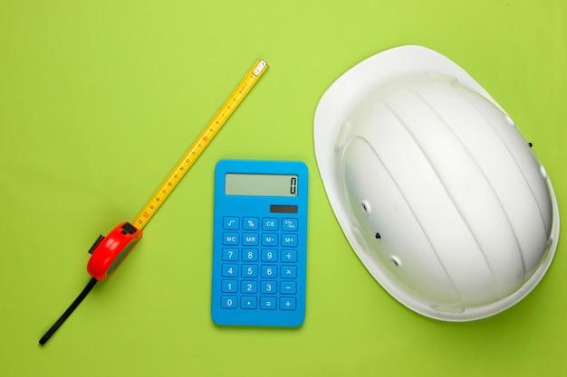 Шлем безопасности инженерного строительства и калькулятор, правитель на зеленом. расчет стоимости ремонта или строительства дома. плоская планировка