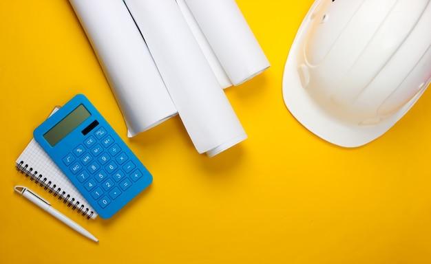 Инженерная строительная защитная каска, рулоны чертежей и калькулятор, тетрадь на желтом. расчет стоимости строительства дома. плоская планировка