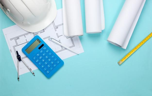 Инженерная строительная защитная каска, рулоны чертежей, план проекта и калькулятор на синем. расчет стоимости строительства дома. плоская планировка
