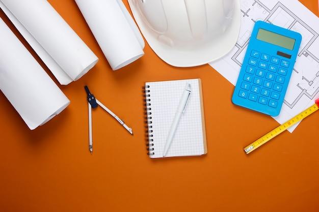 Инженерная строительная защитная каска, рулоны чертежей, план проекта и калькулятор на коричневом. расчет стоимости строительства дома. плоская планировка