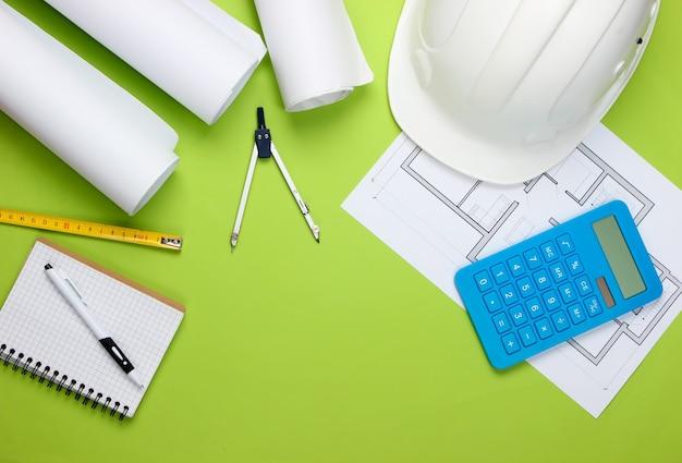 Инженерная строительная защитная каска, рулоны чертежей, план проекта и калькулятор на зеленом. расчет стоимости строительства дома. плоская планировка
