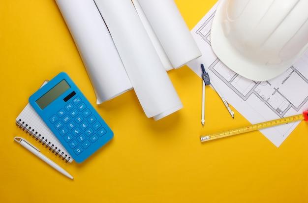 Инженерная строительная защитная каска, рулоны чертежей, план проекта и калькулятор на желтом. расчет стоимости строительства дома. плоская планировка