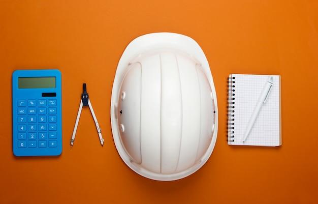 オレンジ色のエンジニアリング建設安全ヘルメット、コンパス、ノートブック、電卓。家の修理や建設の費用の計算。フラットレイ