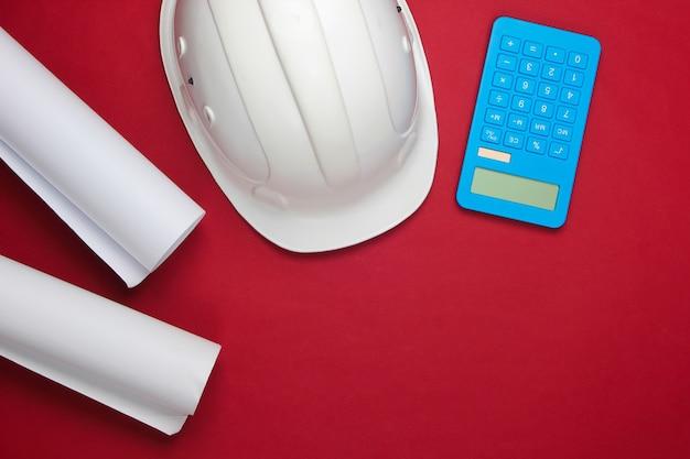 Каска безопасности инженерного строительства, рулоны чертежа и калькулятор на красном. расчет стоимости строительства дома. плоская планировка