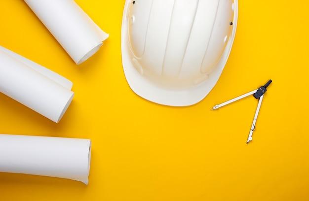 エンジニアリング建設安全ヘルメット、描画ロール、黄色のコンパス。家を建てる。フラットレイ