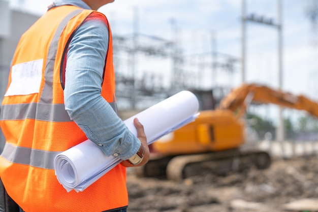 Engineering consulting people on construction site holding blueprint in his hand