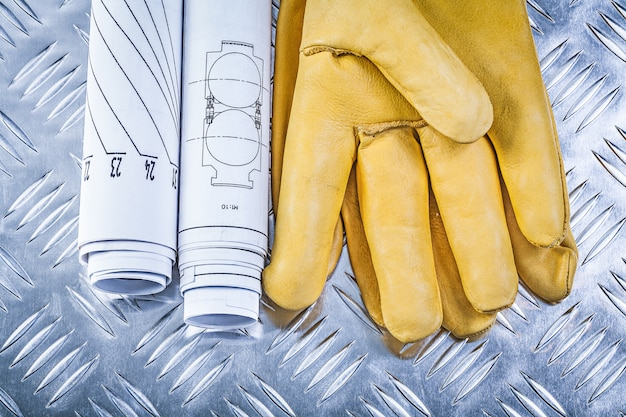 Engineering drawings leather safety gloves on fluted metal sheet construction concept