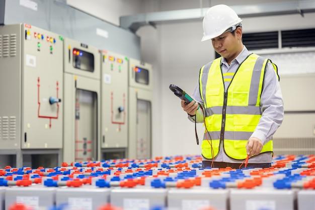 엔지니어링 전기 기술자는 전력실 백업에서 디지털 테스터 배터리를 사용했습니다.
