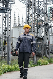 An engineering employee makes a tour and inspection of a modern electrical substation.