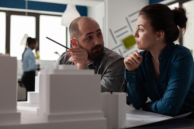 議論しているオフィスに座っている建築家のエンジニアリンググループ