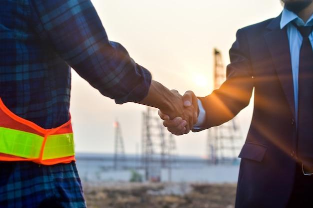 エンジニアリングの手が建物の建設不動産プロジェクトの成功を職場で振る、ビジネスの人々は手契約投資事業を振る