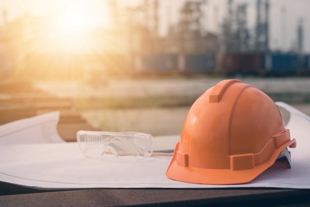 Engineering helmet on blueprint in construction site.
