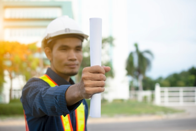 Engineering holding plan and wears a white safety hat while working.