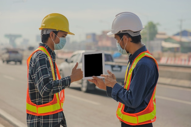 Engineering holding tablet work on road construction, construction engineering use white tablet application working building estate architecture
